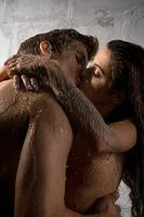 Naked couple embracing and kissing in shower
