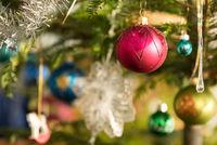 colorful christmas baubles on christmas tree - closeup christmas eve