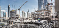 Laborers working on modern constraction site works in Dubai. Fast urban development consept
