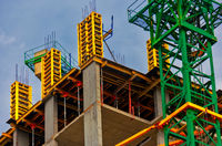 Apartment building construction work site with monolith concrete walls and crane painted in bright green color
