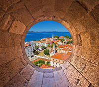 Colorful city of Zadar rooftops and towers view through stone window