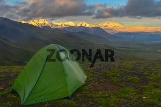 Sunrise view of Mount Denali (mt Mckinley) peak with alpenglow during golden hour with green camping tent in the foreground from Stony Dome overlook. Denali National Park and Preserve, Alaska