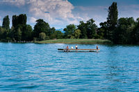 young men relaxing and swimming on a wooden swimming platform in a large lake