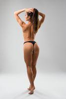 Fitness model wearing black tanga rearview