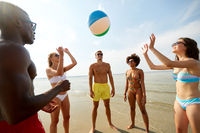 happy friends playing ball on summer beach