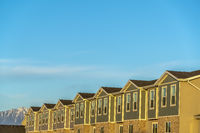 Townhomes against snow topped mountain and bright blue sky on a sunny day