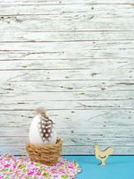 Easter background with Easter egg and cock isolated on blue in front of wood