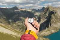 A man's hand holds a pocket magnetic compass for navigation against the backdrop of a rocky slope and a mountain lake. The concept of finding a way. Gaining freedom. freedom of choice