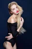 Beautiful blonde woman in a black combidress posing in studio