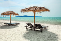 Vacation holidays background - beach lounge chairs under parasols on tropical beach