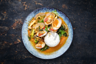 Traditional Thai kaeng phet red curry with clams and rice as top view on a plate