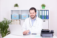 Bearded doctor working at his office. Business and medical concept.