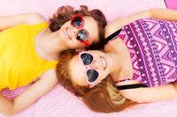 teenage girls in sunglasses on picnic blanket