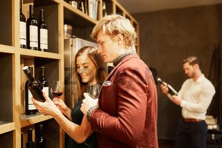 Junges Paar bei einer Weinprobe vor einem Regal