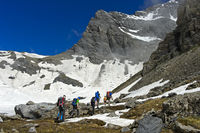 Hikers walking across the Plan Salentse cirque on the way to the Rambert Hut, Valais, Switzerland