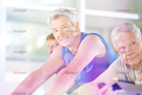 Älterer Mann trainiert auf Fahrrad im Fitnesscenter