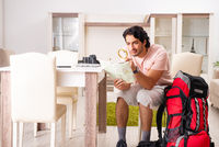 Young male tourist preparing for trip at home