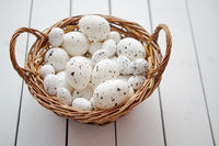 Basket of white dotted Easter eggs in brown wicker basket