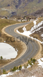 Vertical Highway curving through a mountain with snowy slope in winter