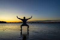 sunrise silhouette of a man on a lake