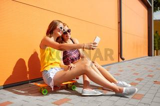 teenage girls with skateboards taking selfie
