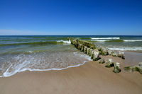 Old wooden breakwater on sandy shore of Baltic sea