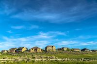 Residential area built on a hill with cloudy blue sky overhead on a sunny day