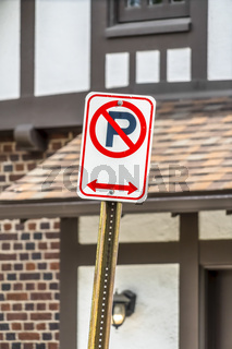 Close up view of a No Parking sign against a building on a sunny day