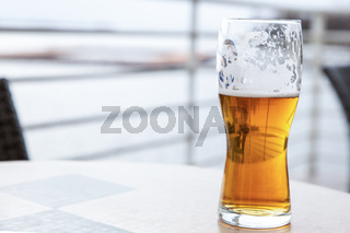 a transparent glass of golden beer drank with foam on the walls, rest in an outdoor cafe