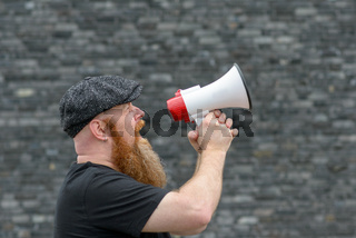 Man yelling into a megaphone at a rally