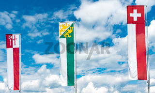 flags and banners of Switzerland and Thurgau and Kreuzlingen under an expressive blue sky with white clouds