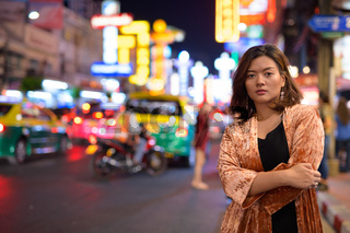Young beautiful Asian tourist woman with arms crossed at Chinatown in Bangkok