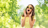 amazed teenage girl in yellow sunglasses