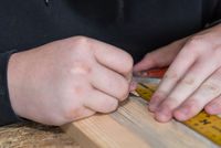 Carpenter measures wood with angle ruler and marks interfaces - close-up