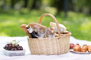 picnic basket, food and wine at summer park