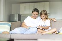 Young mother and her daughter drawing