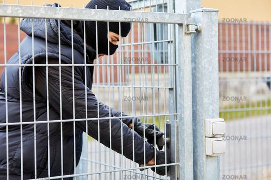 Einbrecher öffnet Türschloss von einem Tor
