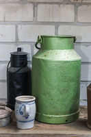 green and rusty milk churns front view