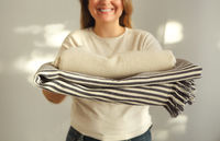 Woman holding stack monochrome white and gray bed linen textiles clothing