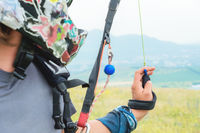Close-up of a professional paraglider holding brakes and looking away. Paraglider sport concept