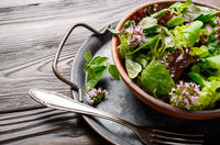 Clay dish with green and violet lettuce, lamb's lettuce salad with oregano flowers on vintage metal tray. Fork aside