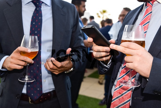Businessmen texting on their mobile phones while holding beer glasses during an entrepreneurs event.