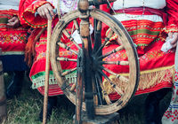 Old wooden spinning wheels and a woman in national dress.