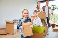 Kinder und Eltern tragen Umzugskartons