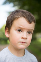 Closeup portrait of thinking freckled boy with dark hair and brown eyes outdoors
