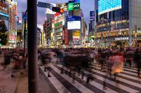 TOKYO, JAPAN - 12 FEB 2018: People walking in Shibuya Crossing with buildings and bright colorful billboards behind