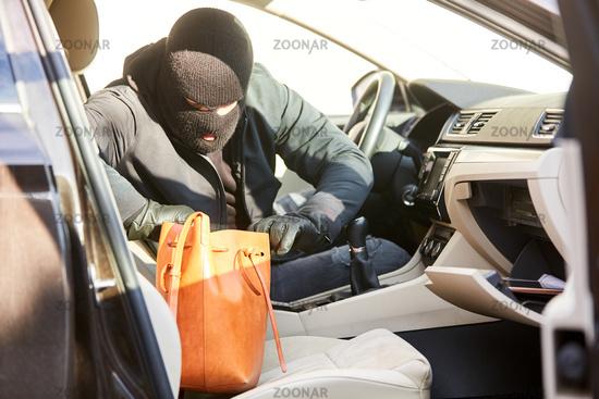 Dieb beim Stehlen aus Handtasche im Auto