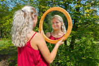 Blond dutch woman looks at mirror in nature
