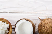 Flat lay background of coconut, coconut shell, hard oil in wooden bowl on white wooden table