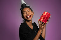 Pretty happy Asian girl in birthday cap holding present isolated over purple wall